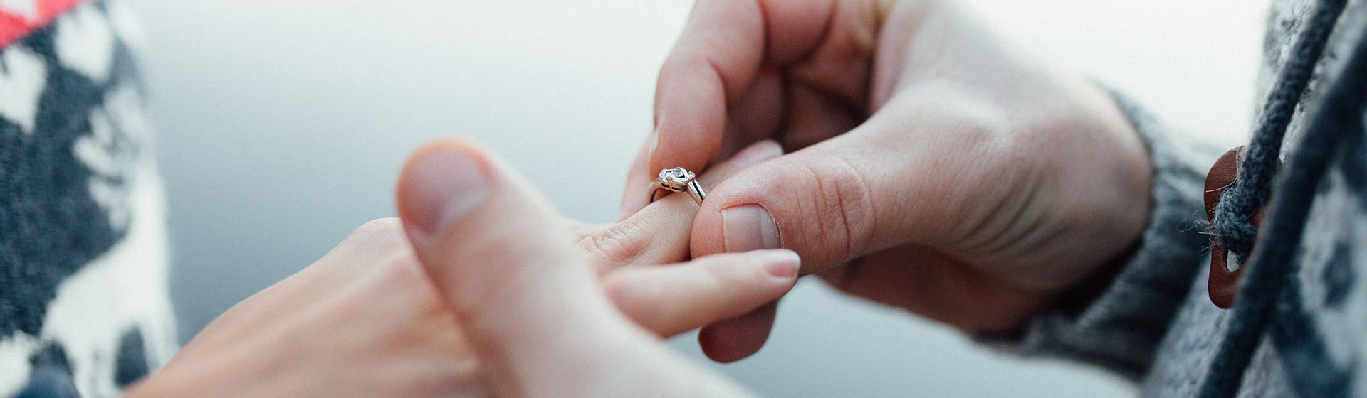 Een man die een ring om de ringvinger schuift bij zijn verloofde | Het Notarieel